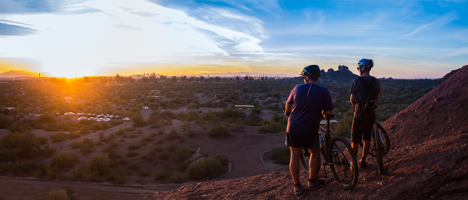 Two men can be seen looking at the horizon on a scene bike trail