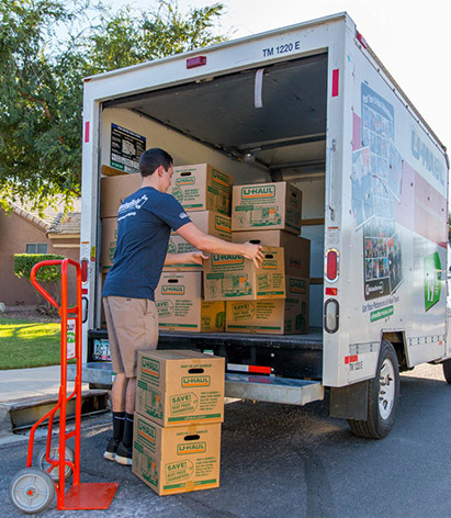 man loading boxes into moving truck