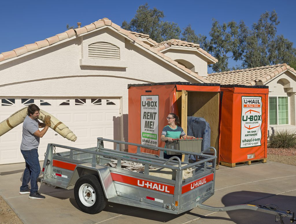 Which house is best: fixer-upper home shows couple outside loading a U-Box container with belongings while they use a trailer to carry renovation supplies, such as a carpet, to the home.