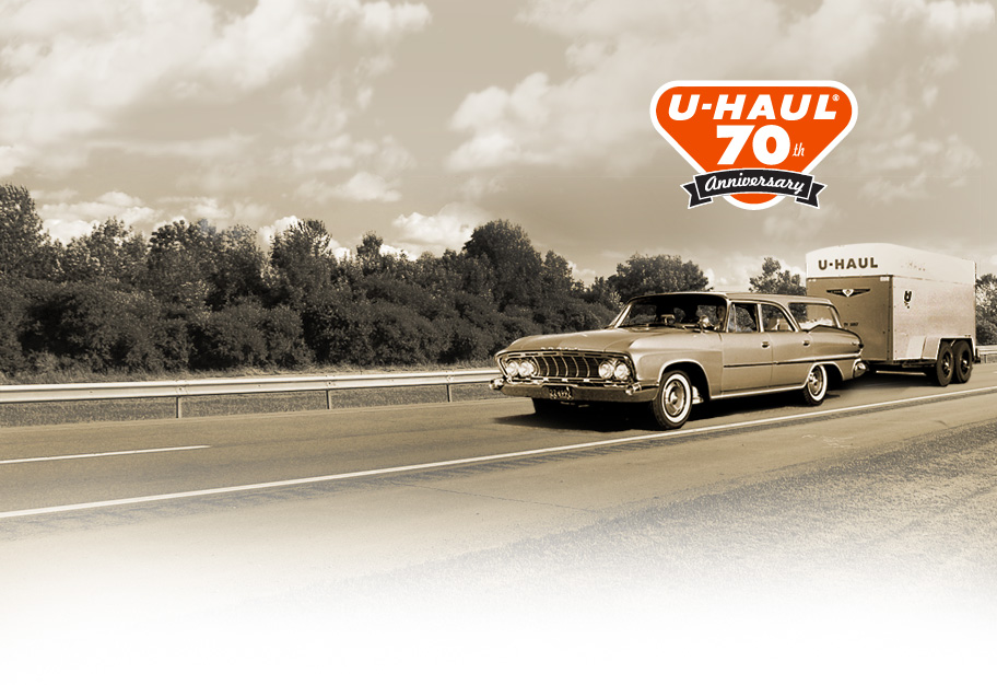 Mid 1950's family sedan towing a uhaul trailer on the highway. U-Haul 70th Anniversay.