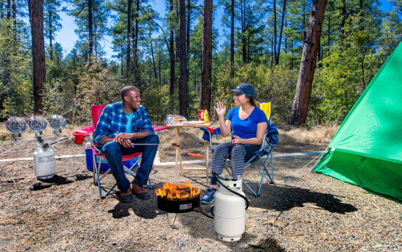Two people grilling food during a camping trip.