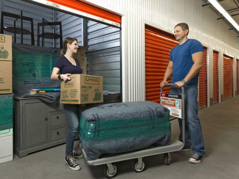 A couple moving things into a U-Haul self-storage unit.
