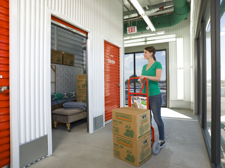 A woman loading boxes into a U-Haul storage unit