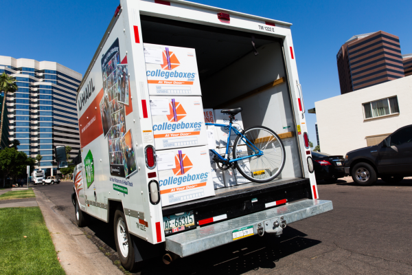 A U-Haul truck containing several stacked Collegeboxes boxes and a bicycle.