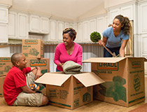 A family placing items into moving boxes.